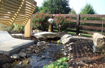 garden stream with a bridge and hardscape by Mobile Joe's Landscaping