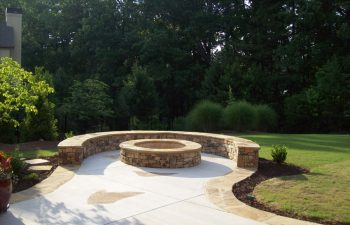 backyard flagstone patio with fire pit by Mobile Joe's Landscaping