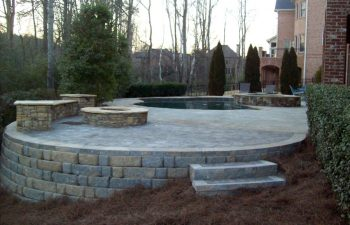 backyard stone patio with fire pit and Koi pond