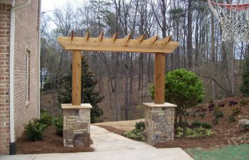 wooden arbor with stone bases by Mobile Joe's Landscaping