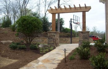 wooden arbor with stone bases and garden stone walkway by Mobile Joe's Landscaping