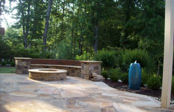 flagstone patio with a fire pit and stone bench