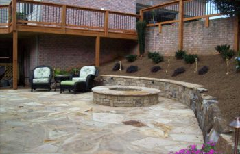 flagstone patio with a fire pit and two garden armchairs